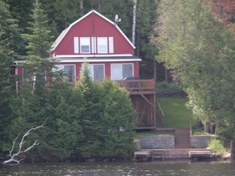Red Cottage with dock and trees as seen from water