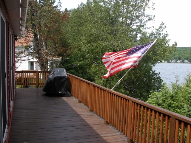 Balcony Patio of the Red cottage with a grill, American flag and view of lake
