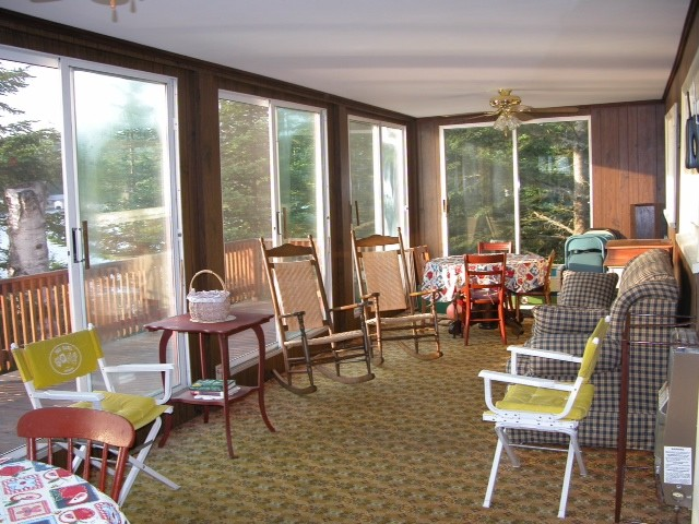 Sunroom / porch of red cottage with large sliding doors going to balcony patio