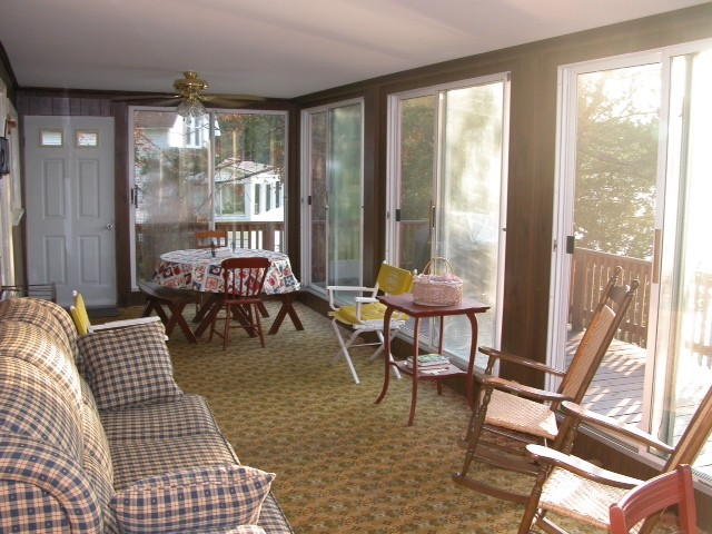 Red cottage enclosed porch / sunroom with furniture