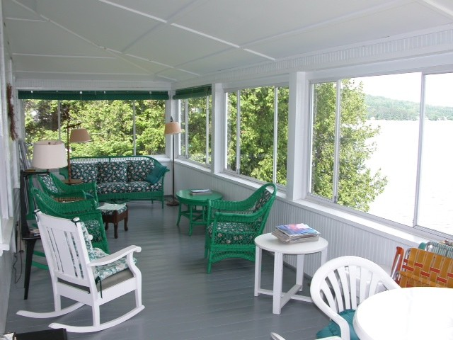 Enclosed porch of white house with white and green furniture