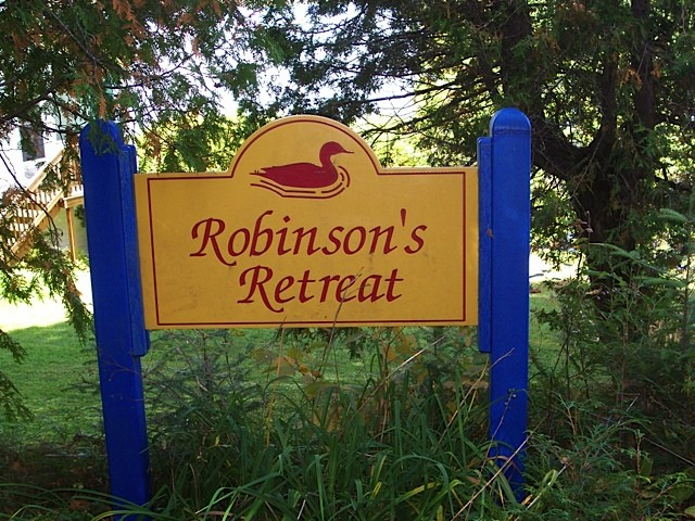 Robinson's Retreat sign in gold with blue posts
