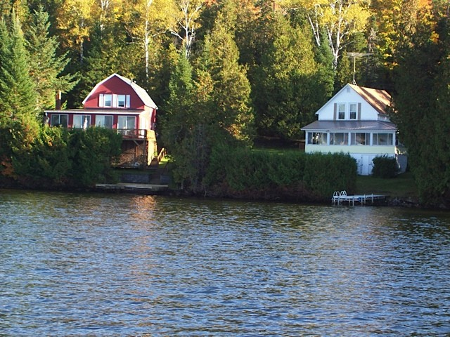The red and white cottage sitting side by side as seen from the water