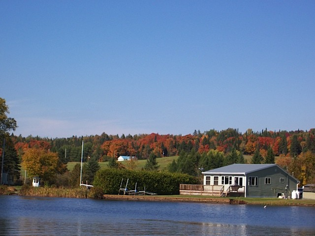 Autumn scene of Joe's Lake with a cottage and trees turning colors