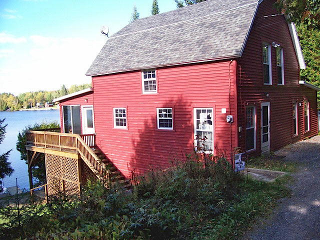 Red cottage with wrap around porch balcony being lit by the sun