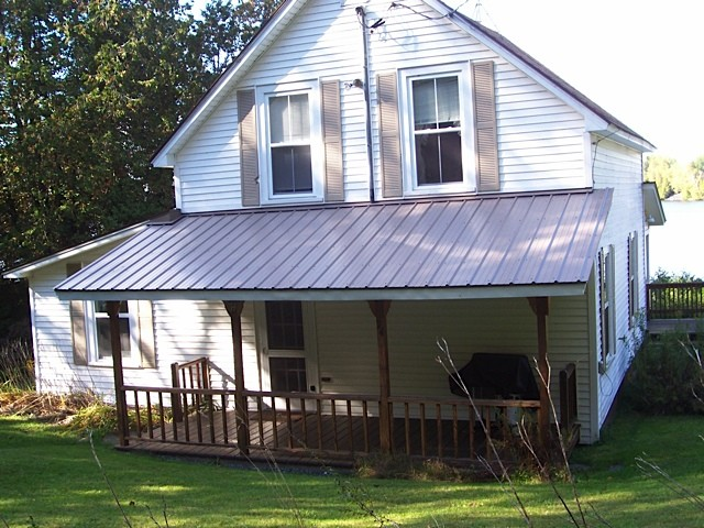 White cottage showing its covered porch