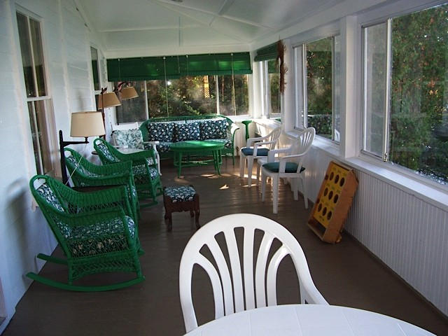 Porch Patio of White Cottage with green and white patio furniture