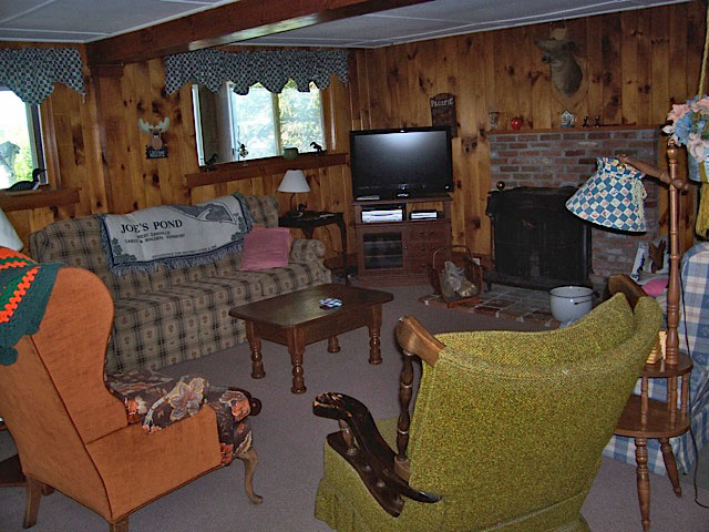 Rustic living room of the red cottage showing tv and sitting area