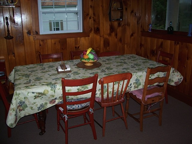 Red cottage dining area with large table and wood plank walls